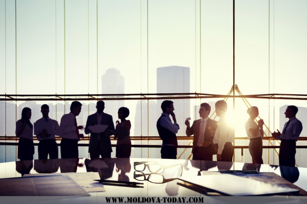Group of business people discussing at sunset reflected onto tab